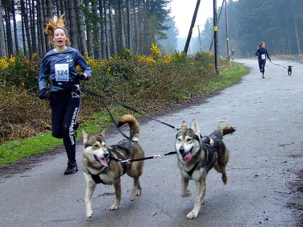 a woman runs with some dogs