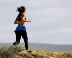 a woman runs accross a cliff top