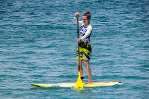 A Women Stand Up Paddle Boarding in the Sea Beach